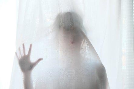 woman behind a curtain