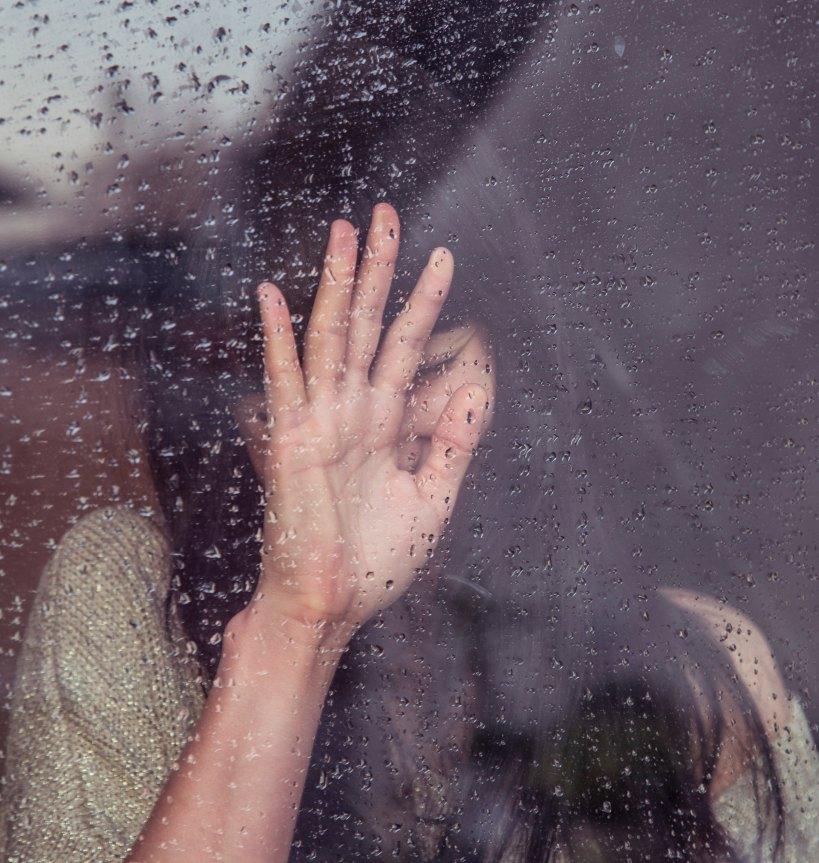 crying woman inside a rainy window
