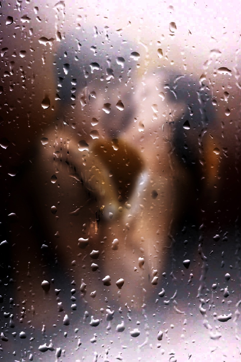 naked couple kissing viewed through raindrops on a window