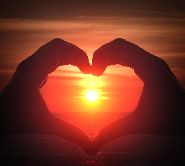 hands forming a heart shape framing a sunset