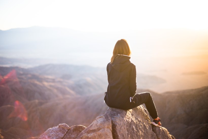 woman sitting atop a mountain
