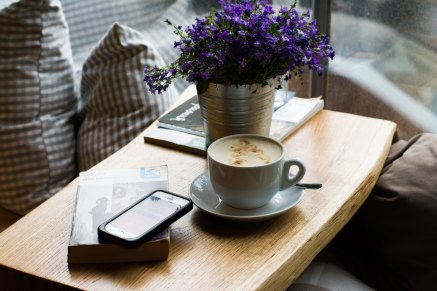 cup of coffee, cell phone, and book sitting on a table