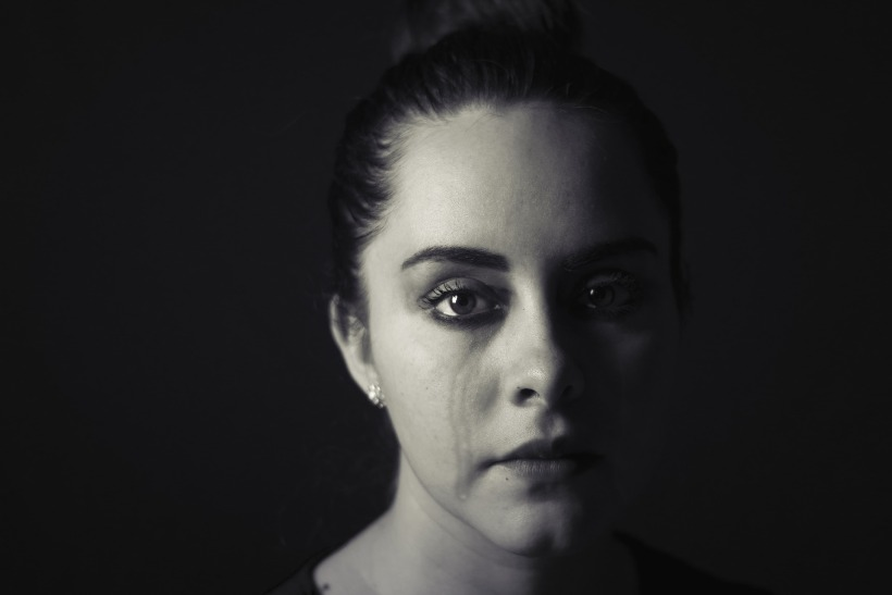 Partly shadowed woman crying