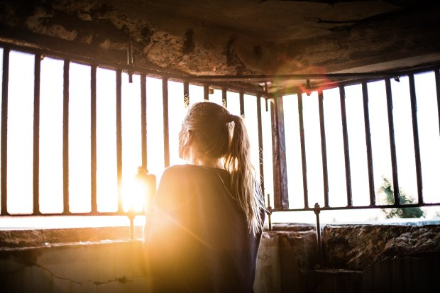 woman looking through barred windows at sunrise