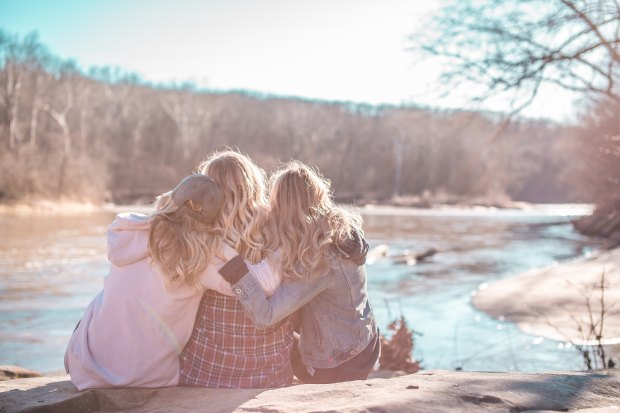 3 women hugging overlooking a river
