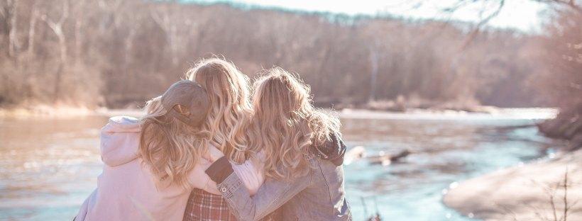 3 women hugging overlooking a river
