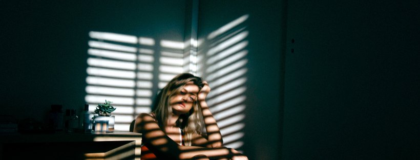 woman sitting in dark room with light shining through blinds