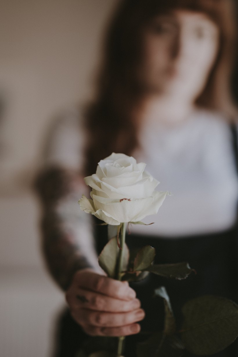 woman holding out a white rose