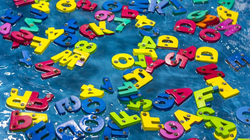 multicolored letters of the alphabet floating in a pool