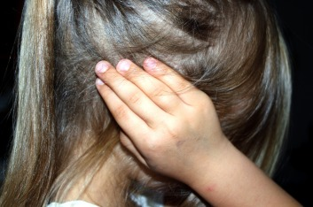 child with hair over face and hands over ears