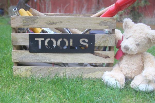 wooden toolbox sitting on grass beside a stuffed bear