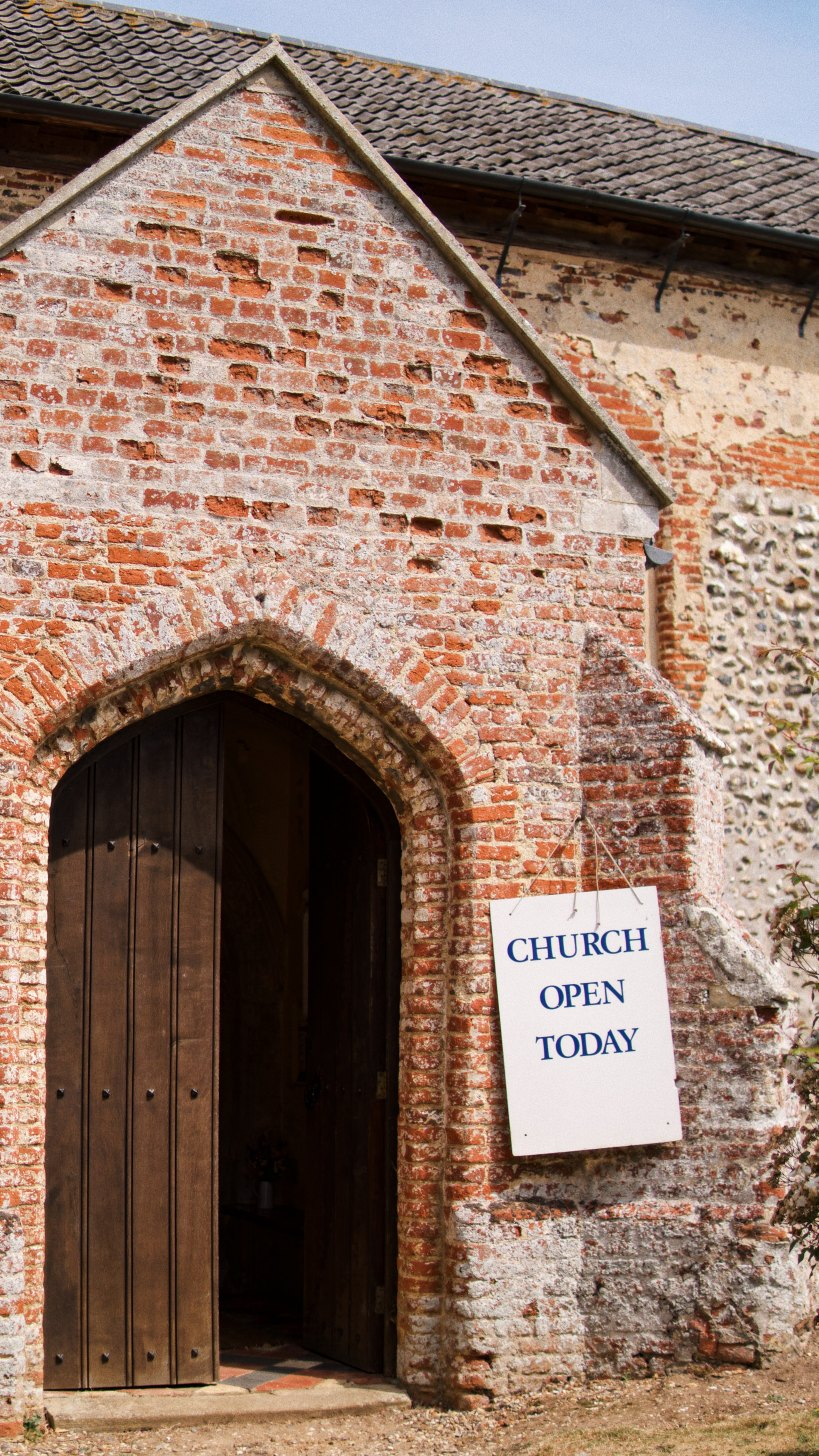 """old brick church with sign """"church open today"""""""