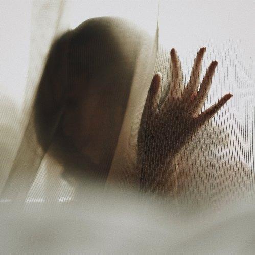 woman partially hidden behind a curtain