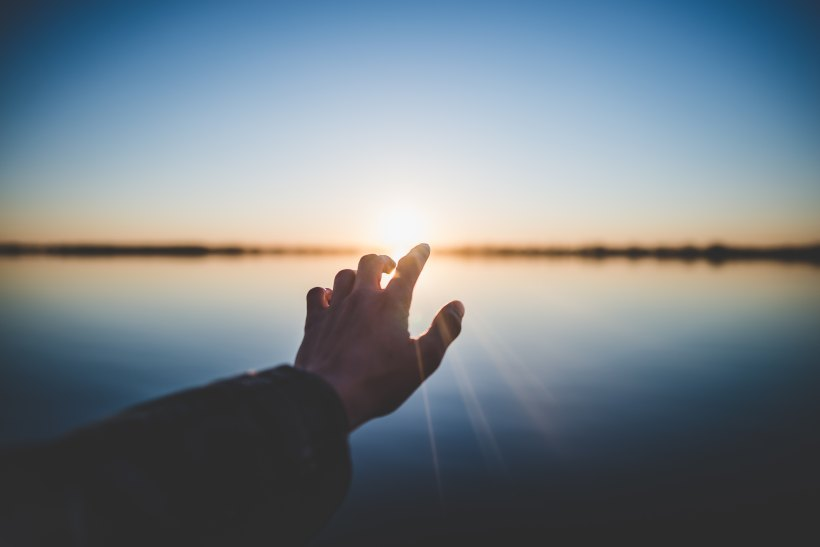 hand reaching towards the sun