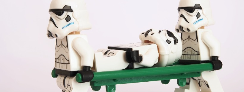 lego stormtroopers carrying a stretcher