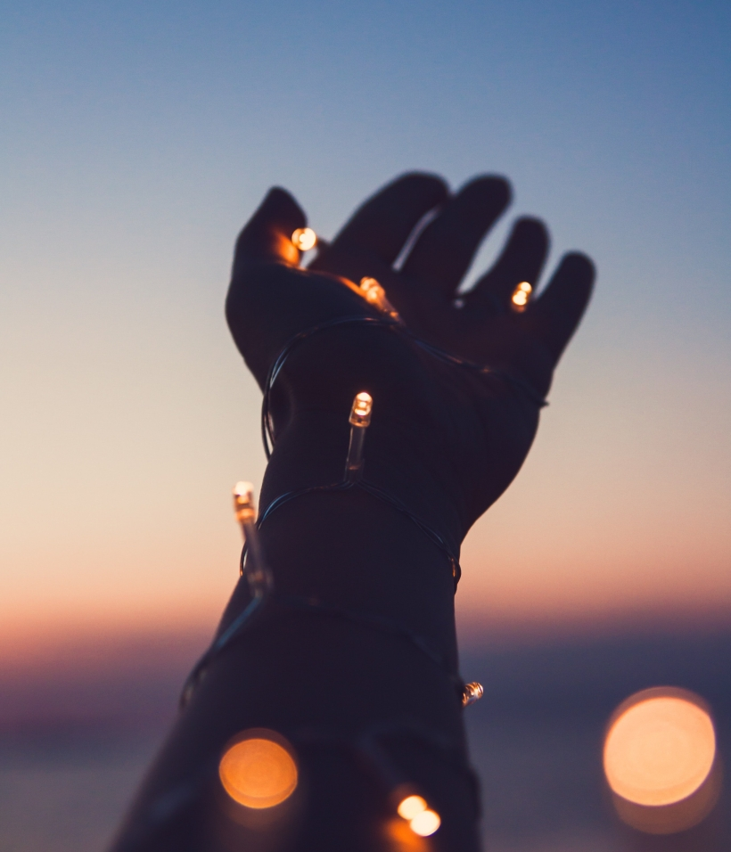 hand wrapped with lights reaching for the sky