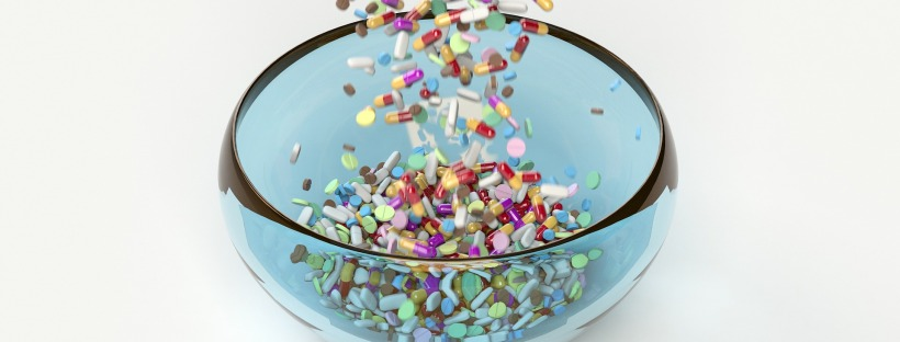 assorted pills being poured into a glass bowl