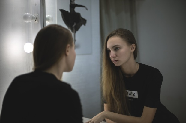 woman looking at her reflection in a mirror