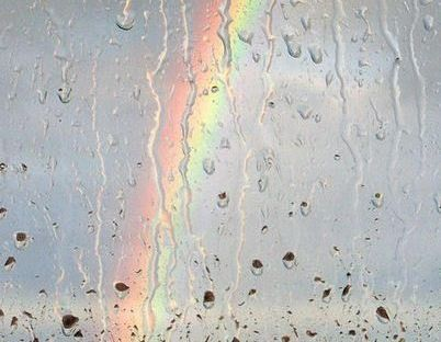rainbow viewed through a rainy window