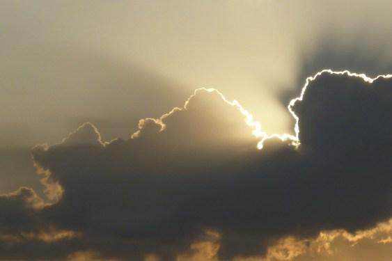 sun shining over dark clouds
